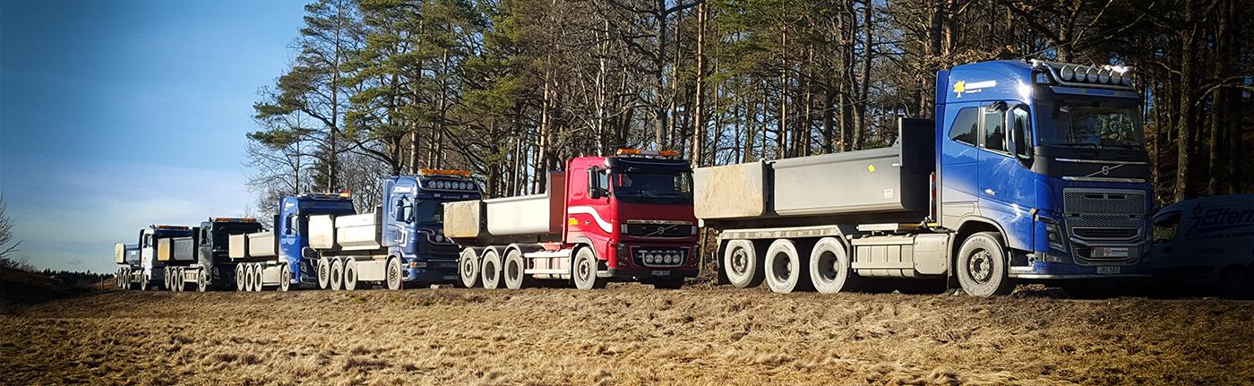 Vår fordonsflotta – anläggningsbilar. Vi har flera lastväxlare/krokbilar som kan byta skepnad och utföra transporter med maskinflak, containers eller grusflak. De flesta har tillhörande släp och kan då även växla flak på släpet.